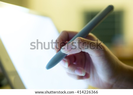 Hand holding a pen touching screen on modern digital tablet - stock photo