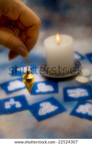 hand holding a pendulum, with an astrological background and candle - stock photo