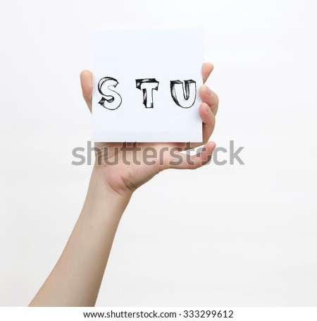 Hand holding a piece of paper with sketchy capital letters S T U, isolated on white. - stock photo