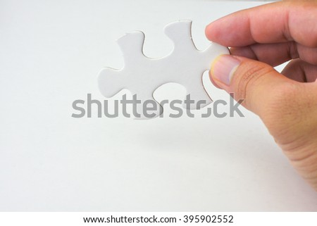 Hand holding a piece of puzzle - stock photo