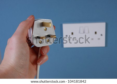 Hand holding a 3 pin plug with socket in the background on a blue wall.  This is a United Kingdom 3 pin plug - stock photo
