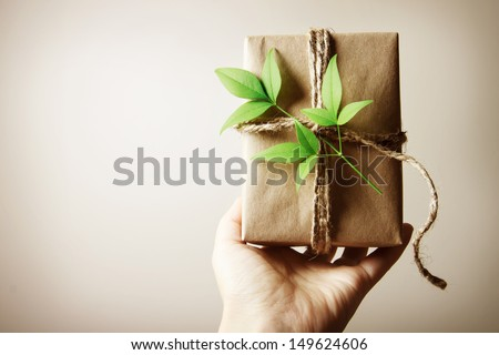Hand holding a present box rustic style - stock photo