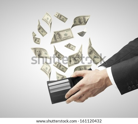 hand holding a purse from which emerge dollars - stock photo