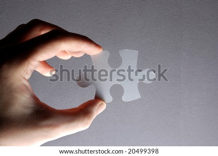 Hand holding a puzzle piece high resolution image