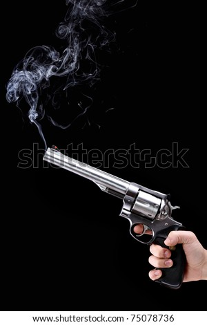 hand holding a revolver with smoking barrel, against black background - stock photo