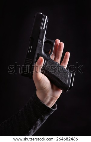 Hand holding a semi automatic handgun (Glock) on a black background