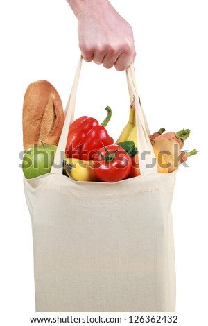 Hand holding a shopping bag filled with groceries such as fruits and vegetables, isolated on white - stock photo