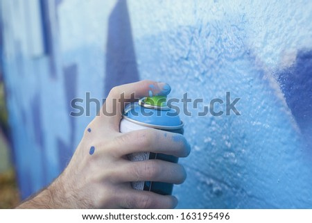 Hand Holding a Spray Paint Can - stock photo