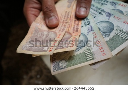 Hand holding a spread of cash in rupee currency. The image was taken in shallow depth of field. - stock photo