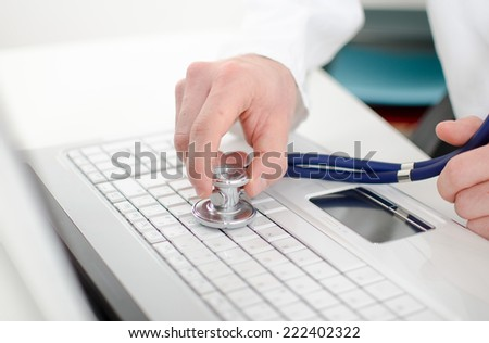 Hand holding a stethoscope on a white laptop keyboard, closeup - stock photo