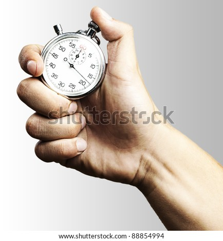hand holding a stopwatch against a grey background - stock photo