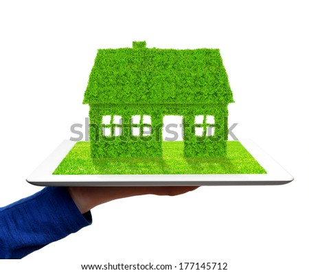 hand holding a tablet with green house