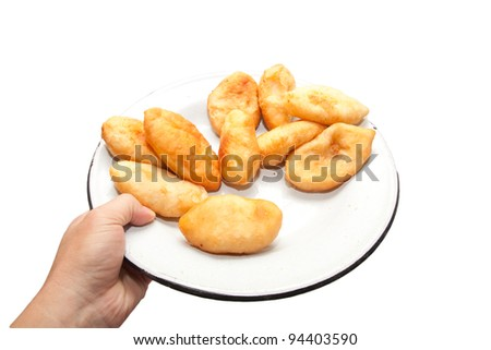 hand holding a tasty pies on a plate isolated on white background. - stock photo