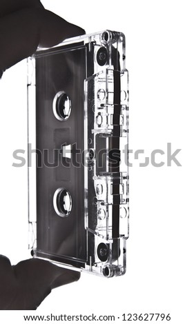 Hand holding a transparent Audio Cassette close up shot - stock photo