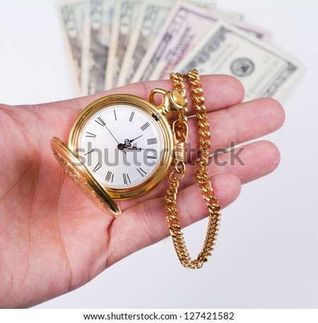 hand holding a watch with money in the background - stock photo