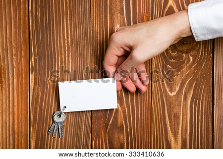 Hand holding a white blank business visit card, gift, ticket, pass, present with keys close up on grunge vintage wooden background. Copy space for text - stock photo
