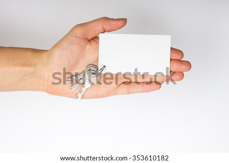 Hand holding a white business visit card, gift, ticket, pass, present close up on white background. Copy space. Real Estate Concept. Top view. - stock photo