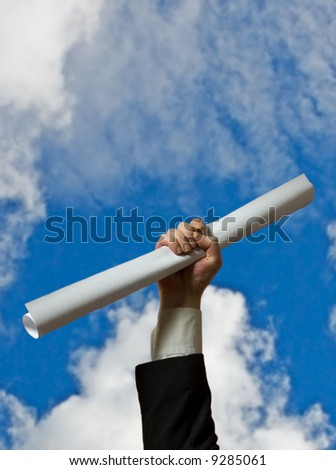 hand holding a white diploma over sky background - stock photo