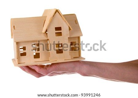 Hand holding a wooden house isolated on white background - stock photo
