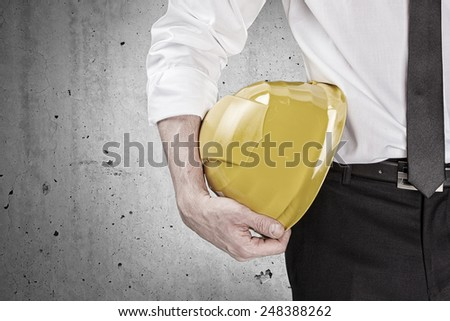 Hand holding a yellow hard hat in front of a concrete wall - stock photo