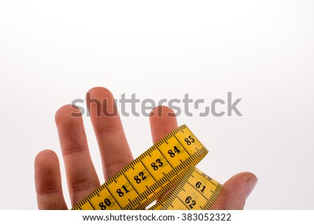 Hand holding a yellow measuring tape