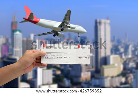 hand holding Airline boarding pass ticket on plane was landing and city background.