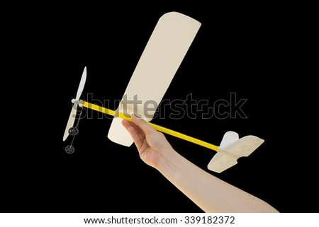 Hand holding airplane plane on black background - stock photo