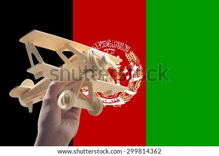 Hand holding airplane plane over Afghanistan flag, travel concept - stock photo