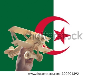 Hand holding airplane plane over Algeria flag, travel concept - stock photo