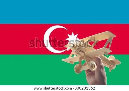 Hand holding airplane plane over Azerbaijan flag, travel concept - stock photo