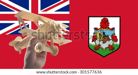 Hand holding airplane plane over Bermuda flag, travel concept - stock photo