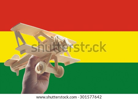Hand holding airplane plane over Bolivia flag, travel concept - stock photo