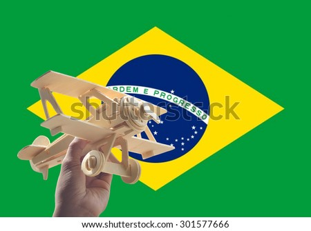 Hand holding airplane plane over Brazil flag, travel concept - stock photo