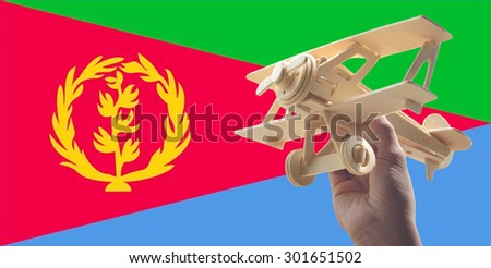 Hand holding airplane plane over Eritrea flag, travel concept - stock photo