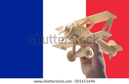 Hand holding airplane plane over France flag, travel concept - stock photo