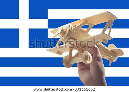 Hand holding airplane plane over Greece flag, travel concept - stock photo