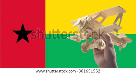 Hand holding airplane plane over Guinea Bissau flag, travel concept - stock photo