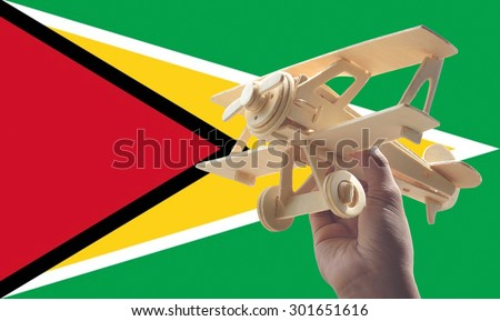 Hand holding airplane plane over Guyana flag, travel concept - stock photo