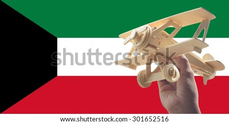 Hand holding airplane plane over Kuwait flag, travel concept - stock photo