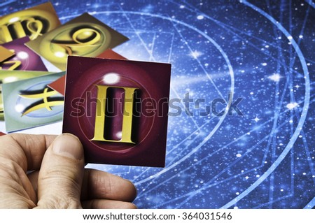 hand holding an astrology card with symbol of sign of Gemini - stock photo