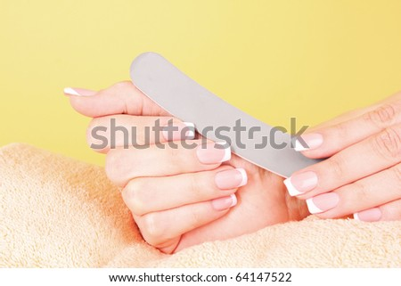 Hand holding an emery board on yellow - stock photo