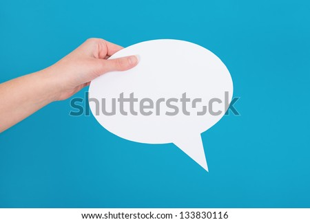Hand holding an empty speech bubble on blue background. - stock photo