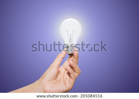 Hand holding an incandescent light bulb - stock photo