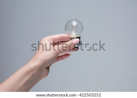 Hand holding an incandescent light bulb on gray background - stock photo