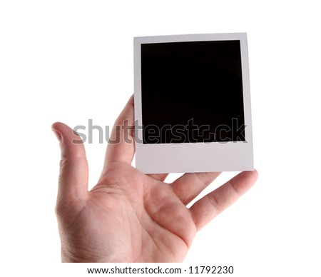 Hand holding an old instant photo film blank isolated on white background