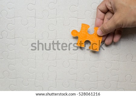 Hand holding an orange jigsaw on the blank puzzle background