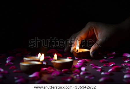 Hand holding and arranging lantern (Diya) during Diwali Festival of Lights  - stock photo