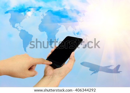Hand holding and touch screen smart phone,cellphone on blue sky with overlay airplane and world map with big sun background