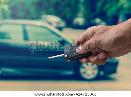 Hand holding and touching the keys over photo blurred of used car for open the door car, transportation and ownership concept, car key concept - stock photo
