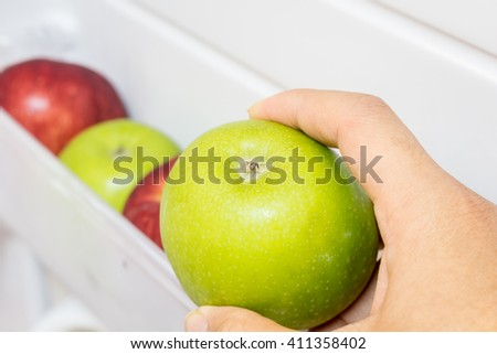 Hand holding apples in refrigerator ideal for diet - stock photo